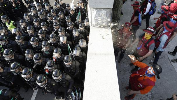 A member of the Korean Confederation of Trade Unions hurls stones at riot police as protesters march toward the presidential house in Seoul