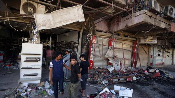 Civilians inspect the site of a bomb attack near restaurants and coffee shops filled with customers in central Baghdad