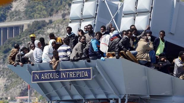 Migrants wait to disembark from an Italian Navy vessel after being rescued from smugglers' boats