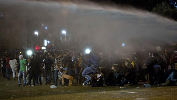Protesters are hit by a water canon as they clash with Israeli riot police in Tel Aviv (AP)