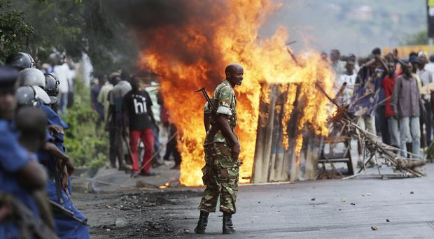 A soldier stands between demonstrators and riot police facing off in the Musaga district of Bujumbura, Burundi (AP)