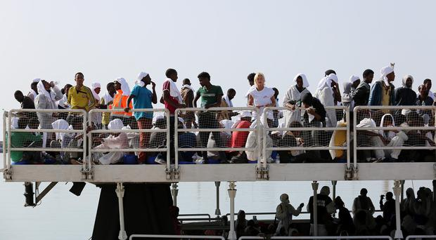 Rescued migrants from a different crossing wait to disembark in the Sicilian harbour of Pozzallo (AP)