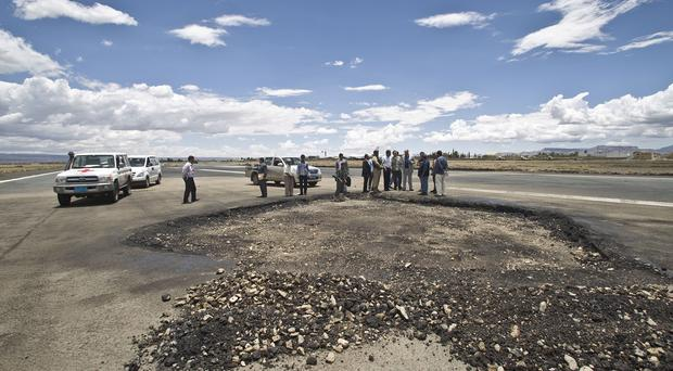 Airport officials and humanitarian workers gather to check damage by Saudi-led air strikes on the runway of the Sanaa International airport, in Yemen (AP)