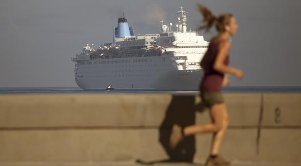 A woman jogs on the Malecon as a Thomson Dream cruise ship arrives in Havana (AP)