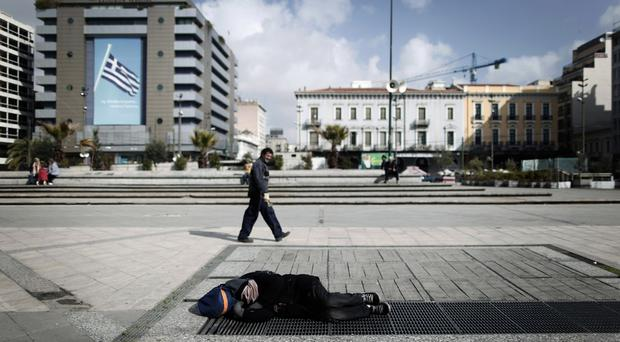 A homeless man sleeps in Omonia Square, central Athens (AP)