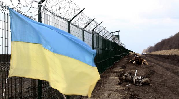 A Ukrainian flag on a razor wire-topped fence intended as the first line of defence against feared armed Russian incursions (AP)