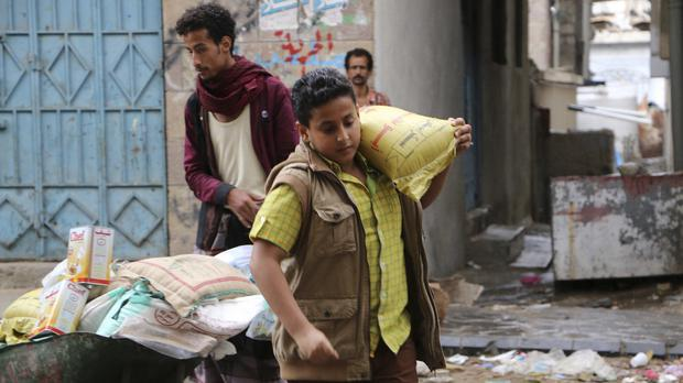 A boy carries a bag of sugar to his family during a food distribution by Yemeni volunteers in Taiz (AP)