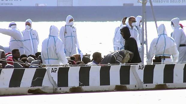 Migrants are seated, surrounded by emergency relief workers, on a vessel at the Italian port of Messina. (AP)