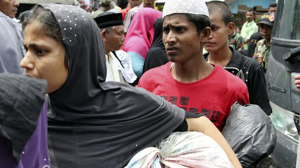 People rescued at sea in Indonesia wait to be transported to a temporary shelter in the Aceh province (AP)