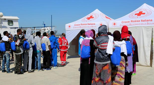 Migrants line up to enter a Red Cross tent after disembarking from the Migrant Offshore Aid Station vessel Phoenix in Sicily, southern Italy (AP Photo/Francesco Malavolta)