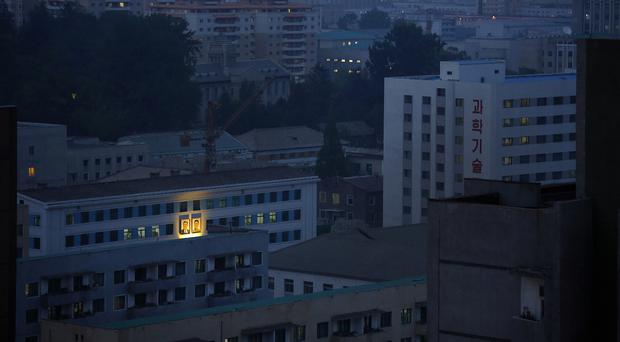 Portraits of the late North Korean leaders Kim Il Sung, left, and Kim Jong Il glow on the facade of a building in Pyongyang (AP)