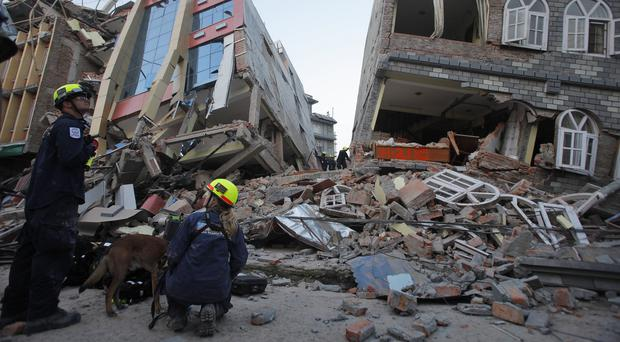 Rescue workers inspect the site of collapsed buildings in Kathmandu (AP)