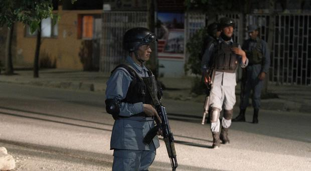 Afghan security forces inspect the site of an attack at the Park Palace Hotel in Kabul (AP Photo/Allauddin Khan)