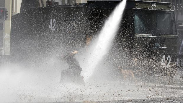 Police operate a water cannon during a student protest in Santiago (AP)