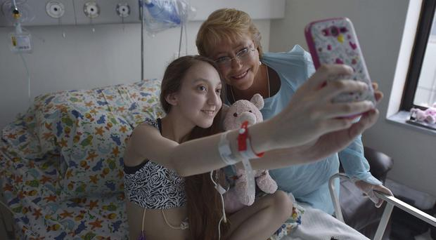 Valentina Maureira takes a photo of herself with President Michelle Bachelet, at the Catholic University hospital in Santiago (AP/Chile Presidential Press Office)