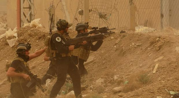 Security forces defend their headquarters against Islamic State extremists during a sandstorm in Ramadi. (AP)