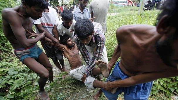 Migrants carry a sick friend toward a temporary shelter after landing in Langsa, Aceh province, Indonesia. (AP)