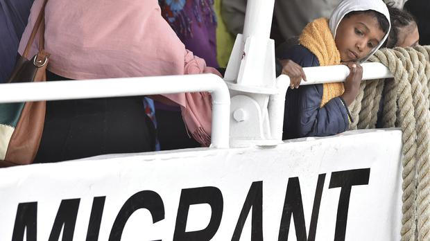 A child waits to disembark from the Migrant Offshore Aid Station vessel Phoenix in the harbour of Messina, Sicily (AP)