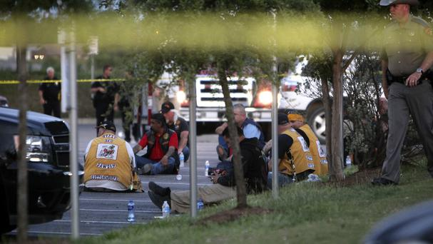 Police detain and watch members of various motorcycle clubs outside the Twin Peaks restaurant in Waco, Texas, after a shootout among rival gangs (AP Photo/John L. Mone)