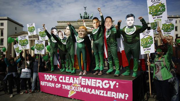 Climate activists wearing masks of the G7 leaders attend a protest in front of the Brandenburg Gate in Berlin (AP)
