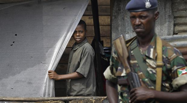 A young boy and a soldier watch demonstrators climb on to a container used as a barricade in Bujumbura, Burundi (AP)