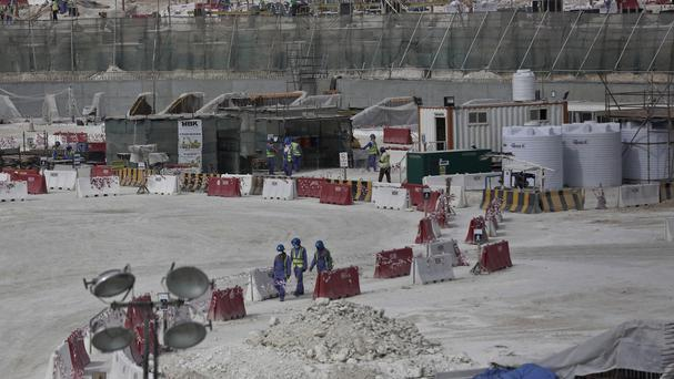 Foreign workers walk between safety barriers at the site of the pitch of the Al-Wakra Stadium that is under construction for the 2022 World Cup in Doha (AP)
