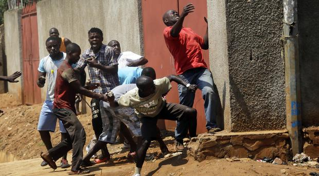 Protester throw stones at police during clashes in the Nyakabyga neighbourhood of Bujumbura, Burundi (AP)