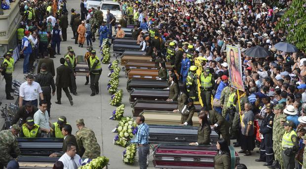 Mourners line up coffins at a funeral mass for victims of the mudslide (AP)