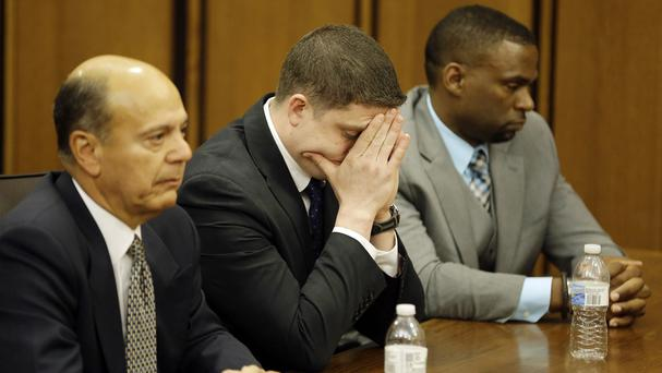 Policeman Michael Brelo, centre, reacts as he is found not guilty over the shooting deaths of two unarmed suspects in 2012 (AP)
