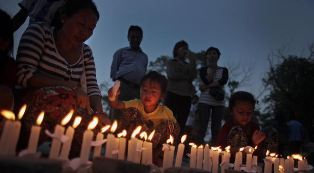 Nepalese people light candles during a vigil to mark the one-month anniversary of the deadly earthquake in Kathmandu (AP)