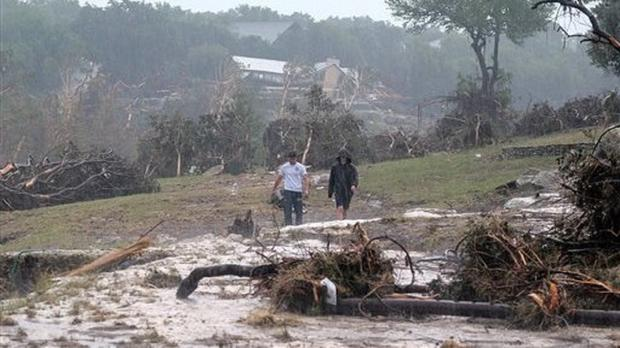 Hudson Doty, 18, left, and Grant Guzal, 17, walk along the bank of the Blanco River in Wimberley, Texas (Rodolfo Gonzalez/Austin American-Statesman via AP)