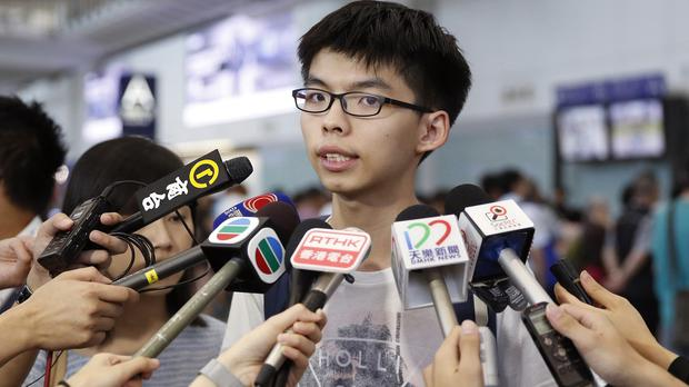 Hong Kong student leader Joshua Wong speaks to the media after arriving at Hong Kong airport (AP)
