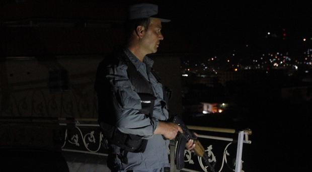 An Afghan security officer takes a position near an attack on a guesthouse in Kabul. (AP)