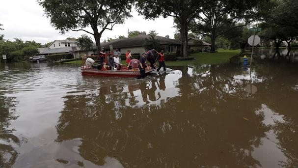 Residents are evacuated by Houston Fire Department from floodwaters surrounding their homes. (AP)