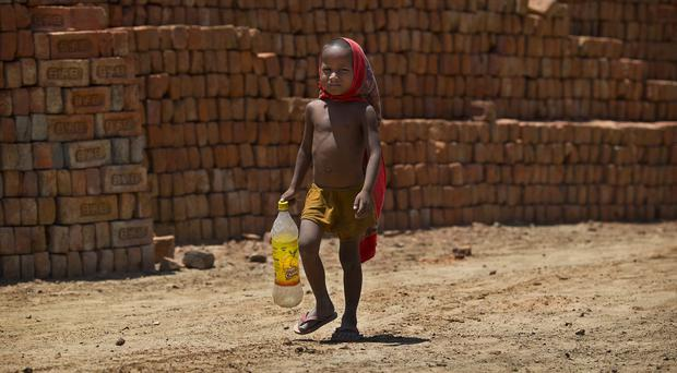 A young boy walks to a water pump to fill his bottle with drinking water (AP)