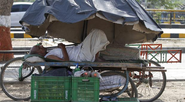An Indian man rests on a hand cart under a market umbrella on a hot day in Ahmadabad, India (AP Photo/Ajit Solanki)