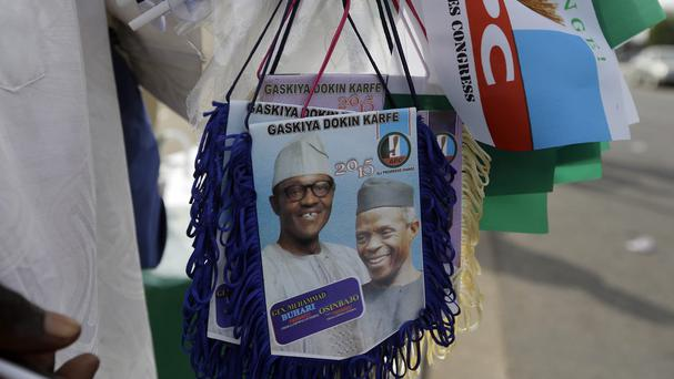 A man sells banners of former general and Nigerian president-elect Muhammadu Buhari and vice president-elect Yemi Osibajo ahead of the presidential inauguration in Abuja (AP Photo/Sunday Alamba)