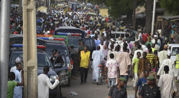 People throng the streets near the site of an explosion in Maiduguri, Nigeria (AP)