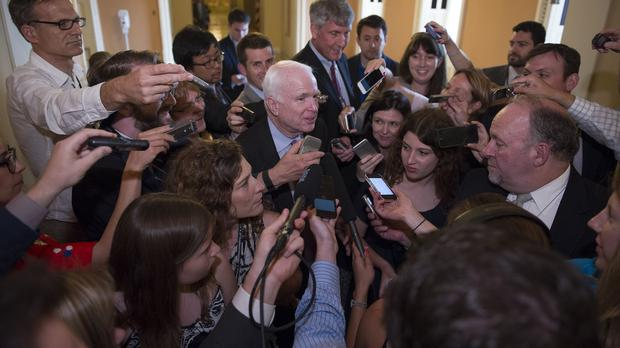 Senator John McCain is surrounded by reporters as he walks to the Senate Chamber (AP)