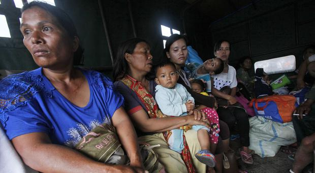 Villagers sit in a truck as they evacuate their homes on the slope of Mount Sinabung in Karo, North Sumatra, Indonesia. (AP)