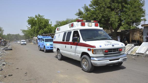 An ambulance and security cars drive to the site of a suicide bomb attack at a market in Maiduguri, Nigeria (AP)