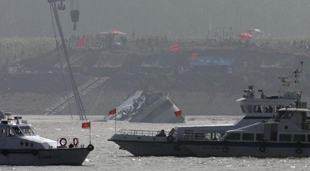 Marine boats patrol as a capsized ship is righted by cranes on the Yangtze River (AP)