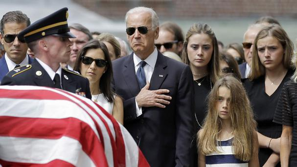 Joe Biden holds his hand over his heart as he watches a casket containing the remains of his son Beau into a church in Wilmington, Delaware (AP)