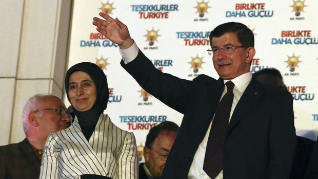 Turkey's Prime Minister Ahmet Davutoglu, accompanied by his wife Sare Davutoglu, waves to supporters in Ankara (AP)
