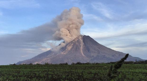 Mount Sinabung spews volcanic material from its crater in Tanah Karo, North Sumatra, Indonesia (AP)