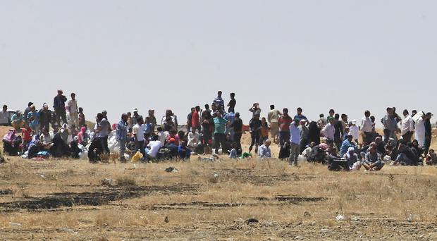 Refugees wait on the Syrian side of the border in order to cross into Turkey. (AP)