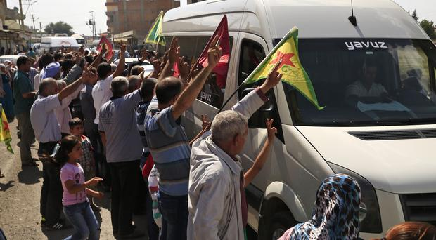 Kurdish people hail the convoy carrying the body of US citizen Keith Broomfield. (AP)