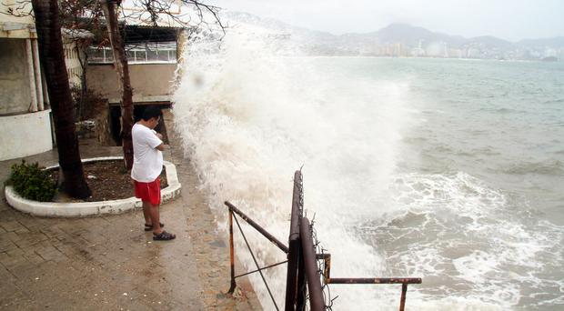 Waves crash against a sea wall in the Pacific resort city of Acapulco, Mexico. (AP)