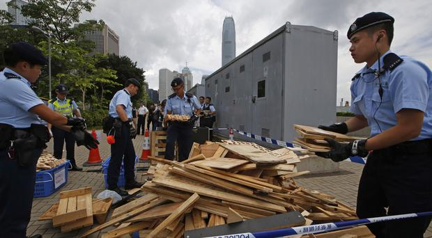 On Saturday, police removed wood from protesters' tents outside the Legislative Council in Hong Kong (AP)