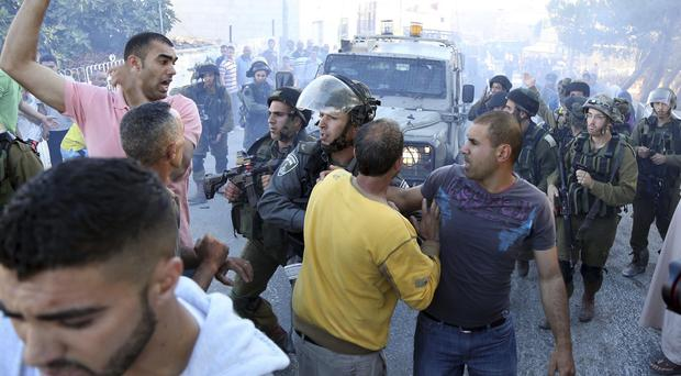 Palestinians scuffle with Israeli soldiers after a Palestinian was killed in the village Kafr Malik, near the West Bank city of Ramallah (AP)